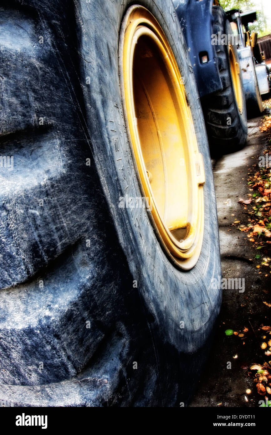 Stylized image of huge bulldozer tires lined up along a street during construction project - Stock Image
