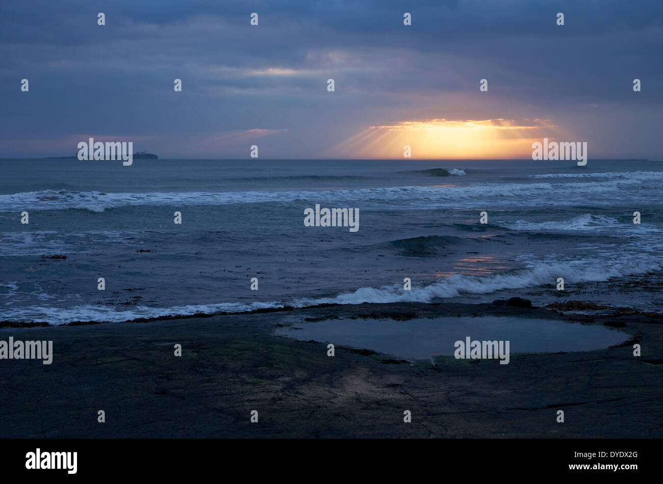 Sunrise and Farne Islands. The shape of the early sun's rays are very suggestive of godly presence. Stock Photo