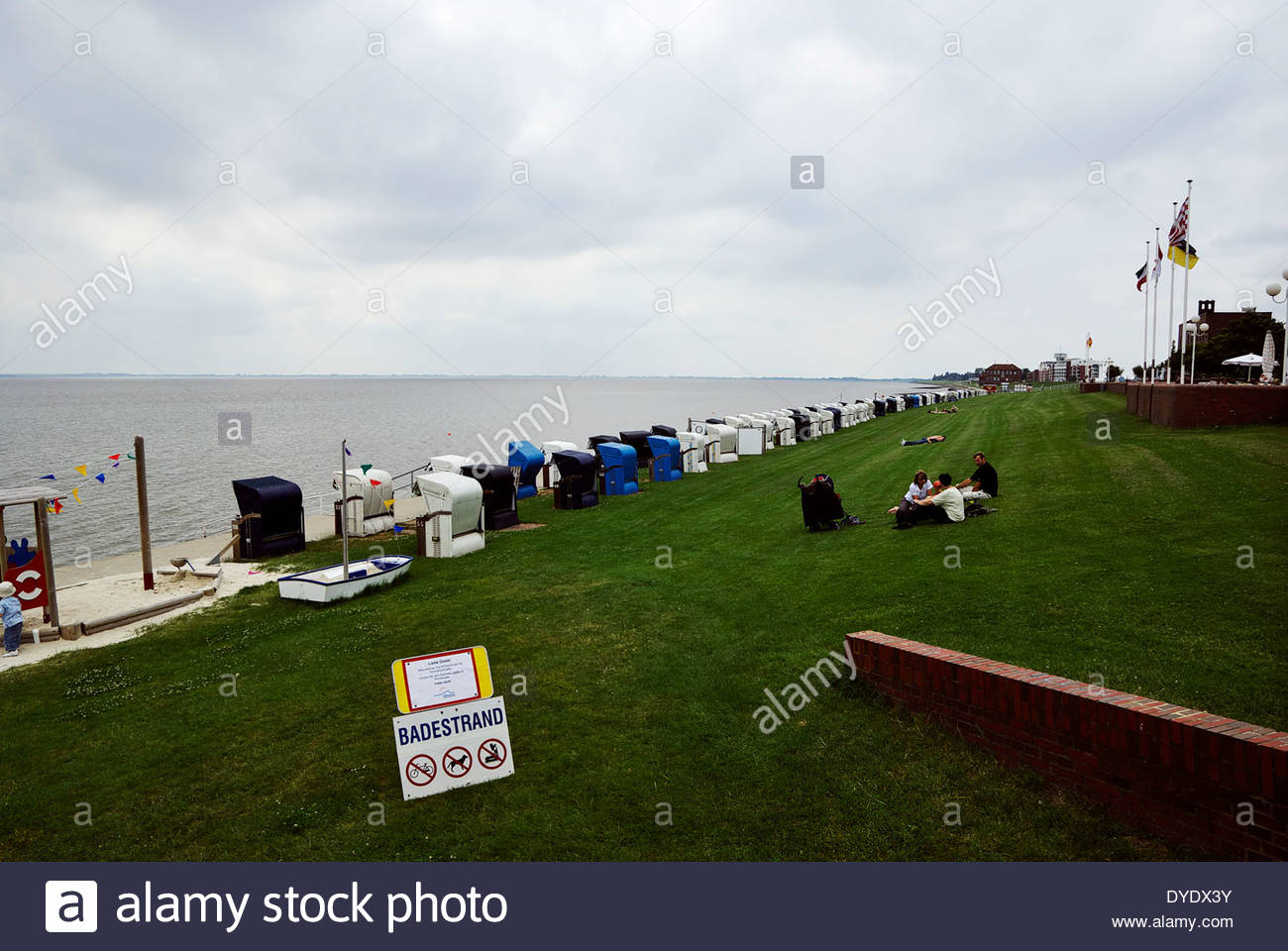 People relax on lawn and in Strandkörbe (beach chairs) on Badestrand bathing beach on Jadebusen (Jade Bight). - Stock Image