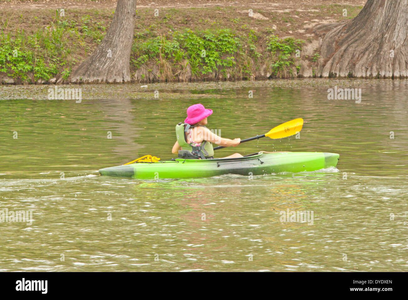 Woman wearing personal floatation device PFD paddling kayak in river Stock Photo