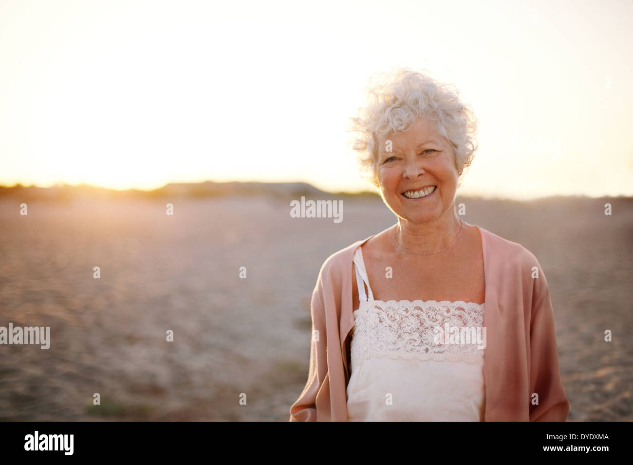 Portrait of cheerful old woman standing on the beach. Smiling senior caucasian female smiling outdoors. Stock Photo
