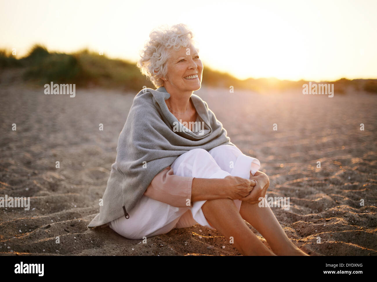 Happy retired woman wearing shawl sitting relaxed on sand at the beach. Senior caucasian woman sitting on the beach outdoors - Stock Image