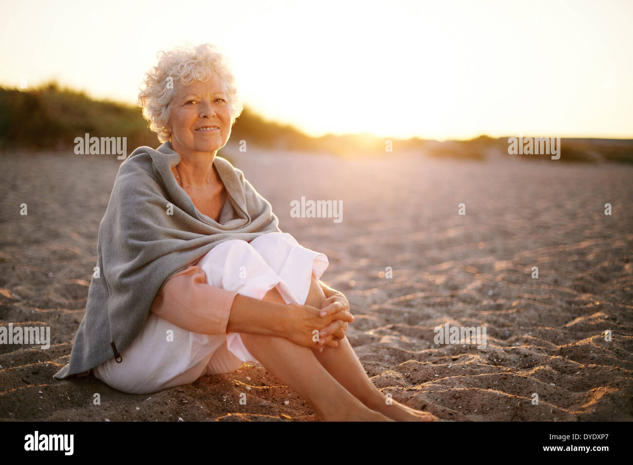 Relaxed retired woman wearing shawl sitting on sandy beach. Old caucasian woman sitting on the beach looking at camera outdoors - Stock Image