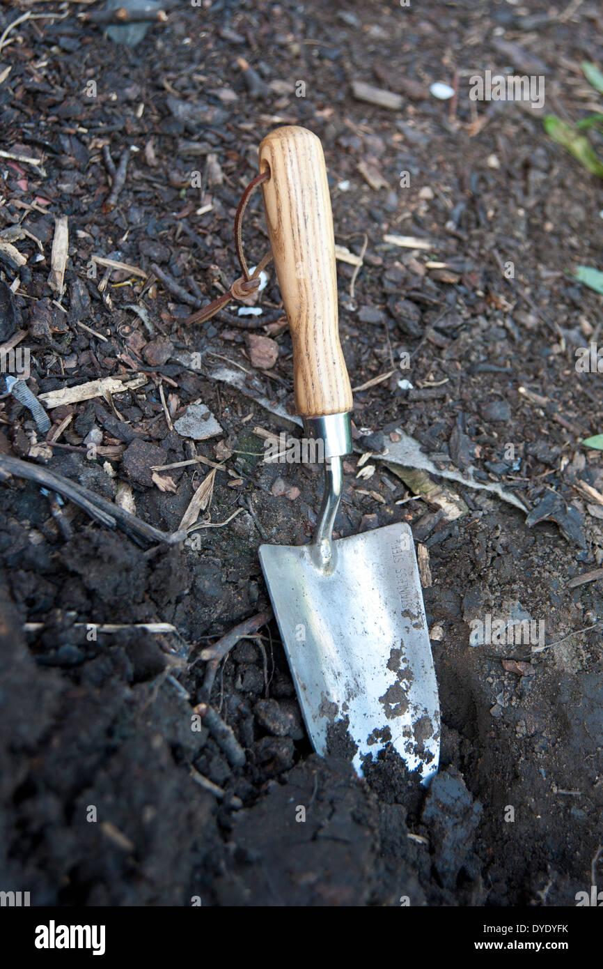 a spade/shovel in a garden - Stock Image