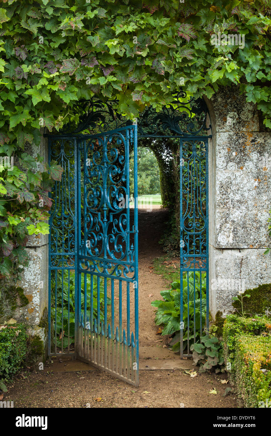 ornate wrought iron gate trapped the ornate wroughtiron gate to the walled garden of rousham house set in cotswold stone arch and framed by vine leaves oxfordshire england house