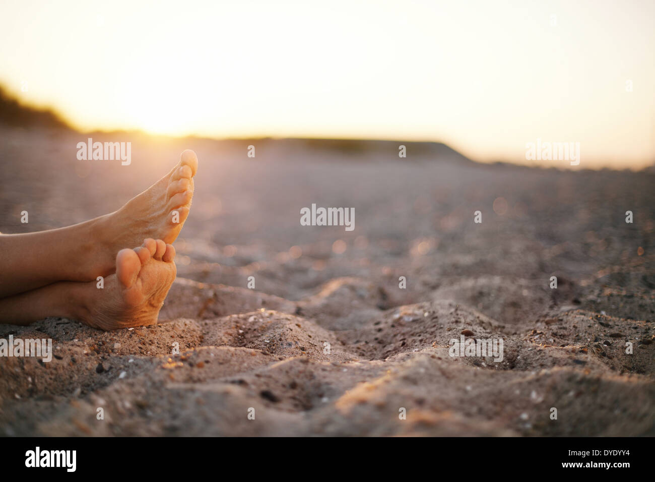 Closeup image of feet of old woman sitting relaxed on sandy beach. - Stock Image