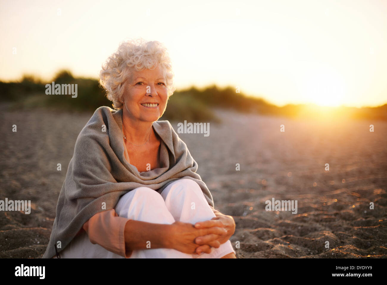 Portrait of smiling old woman sitting on the beach. Senior caucasian female relaxing outdoors - Stock Image