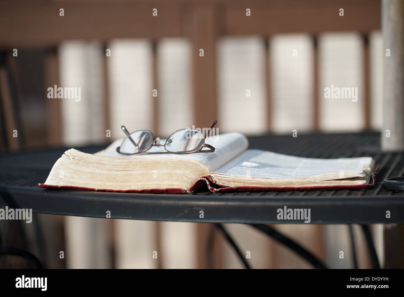 A pair of reading glasses lies on top of an open Bible laying on a wrought iron table on a wooden deck with matching chairs. - Stock Image