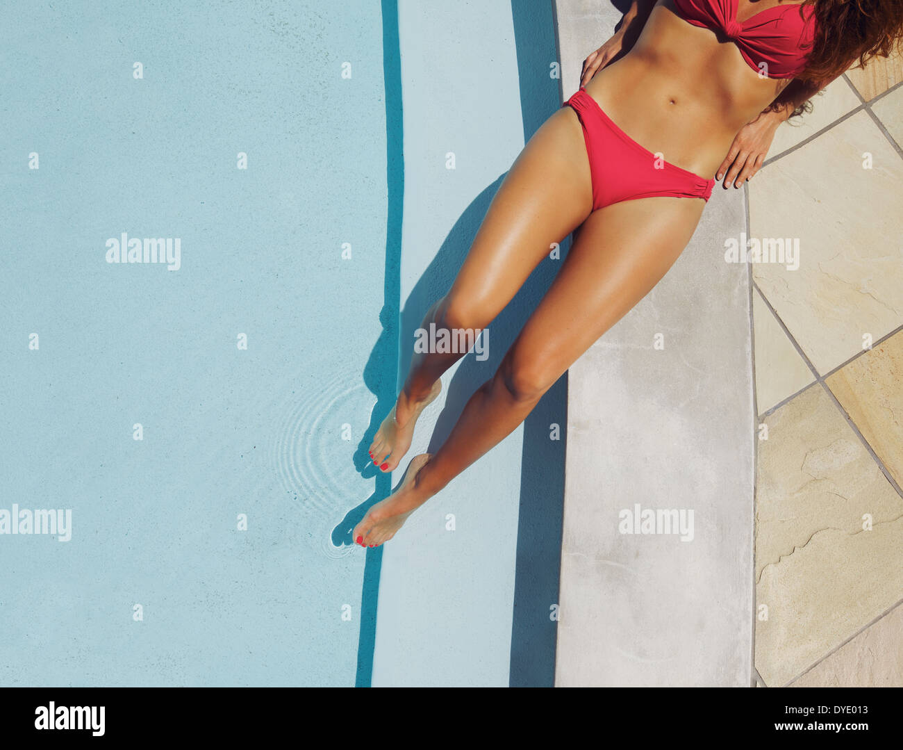Overhead view of a beautiful female fashion model wearing red bikini resting on the edge of a pool at a luxury resort. Stock Photo