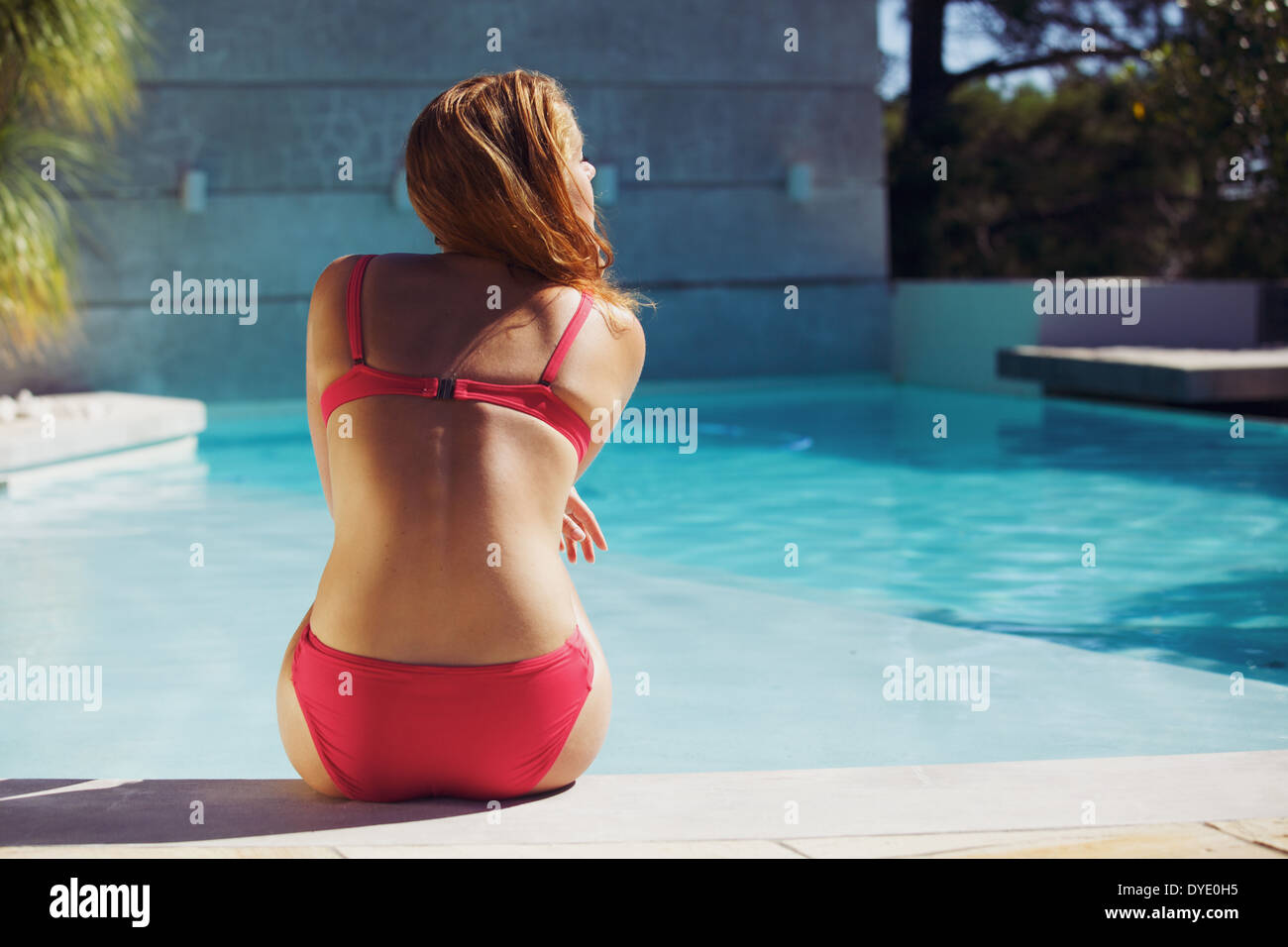 Young woman wearing red bikini enjoying summer at the swimming pool. Caucasian female model sitting on the edge of the pool. - Stock Image