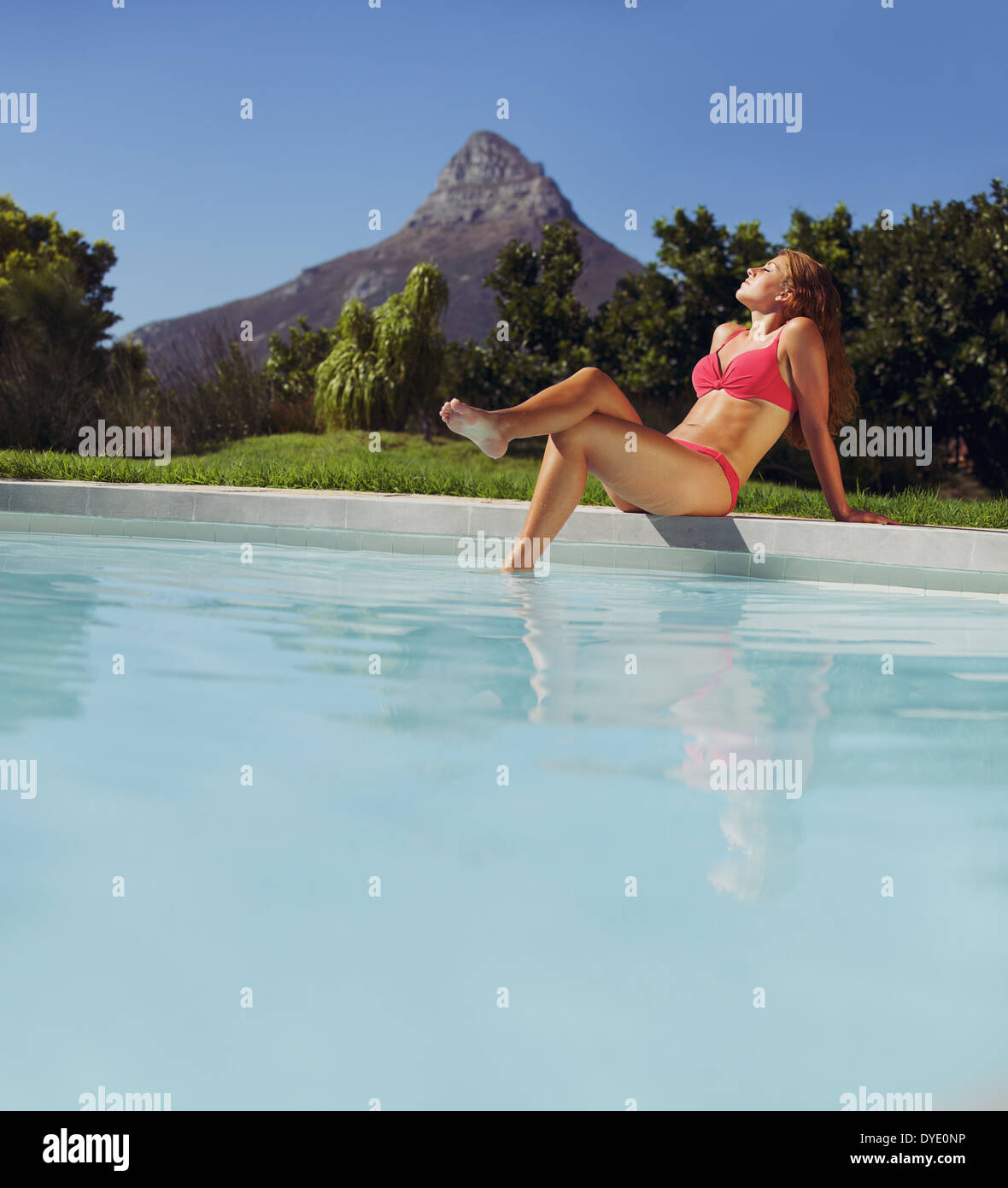 Beautiful young woman sitting by swimming pool and enjoying a sunbath. Caucasian female model in bikini sunbathing by poolside. - Stock Image