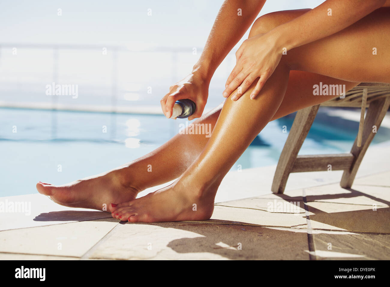 Woman sitting on deck chair by the swimming pool spraying suntan lotion onto her legs - Stock Image
