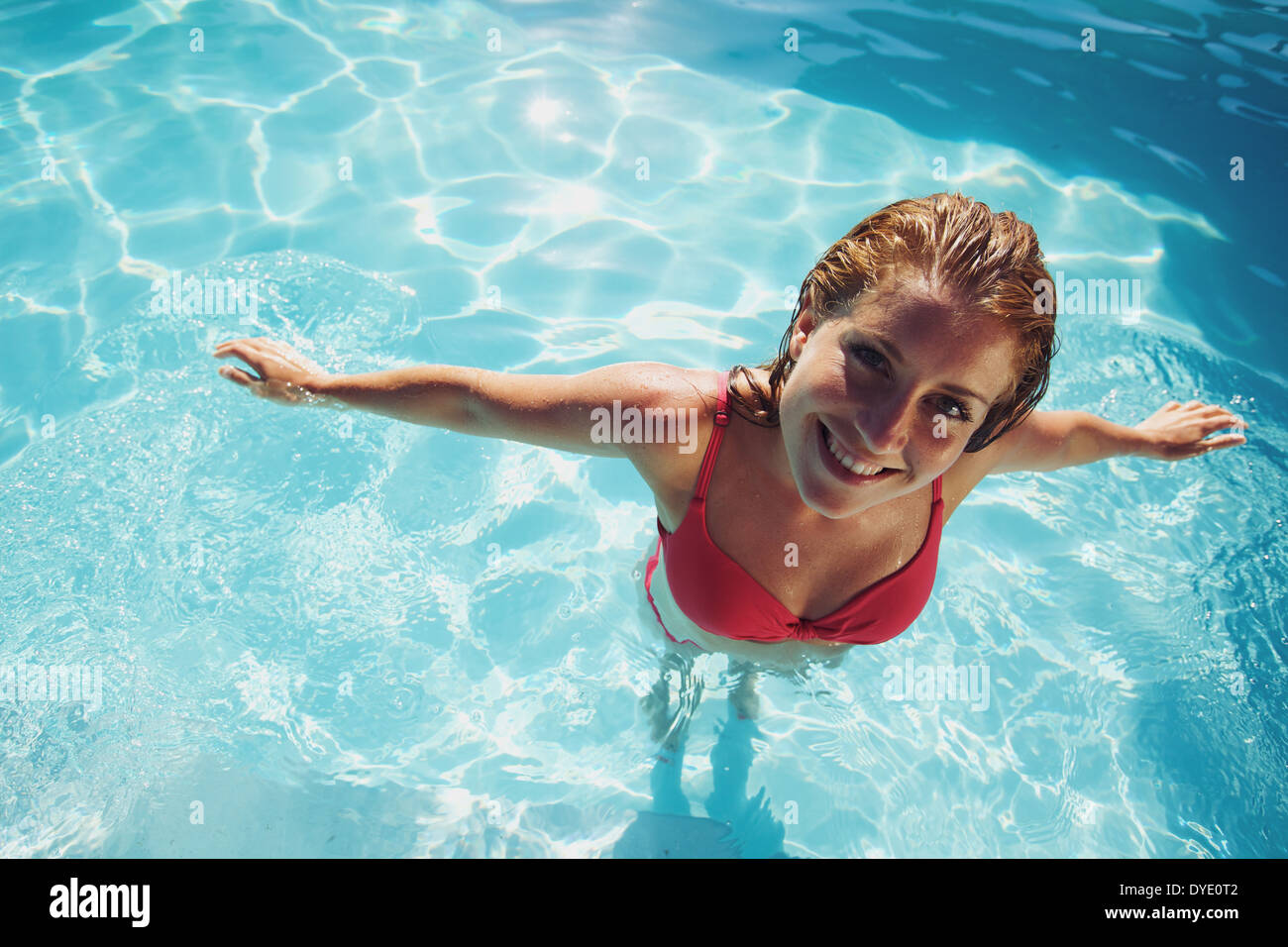Portrait of a beautiful young woman in a swimming pool looking at camera. Pretty caucasian female model in swimwear. - Stock Image