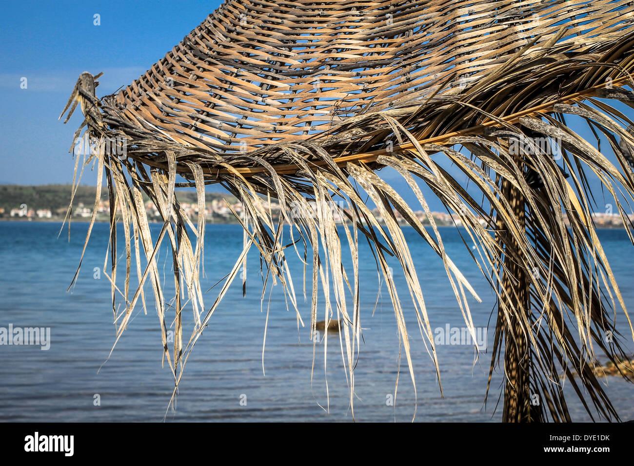 Straw umbrella with blue sea background - Stock Image