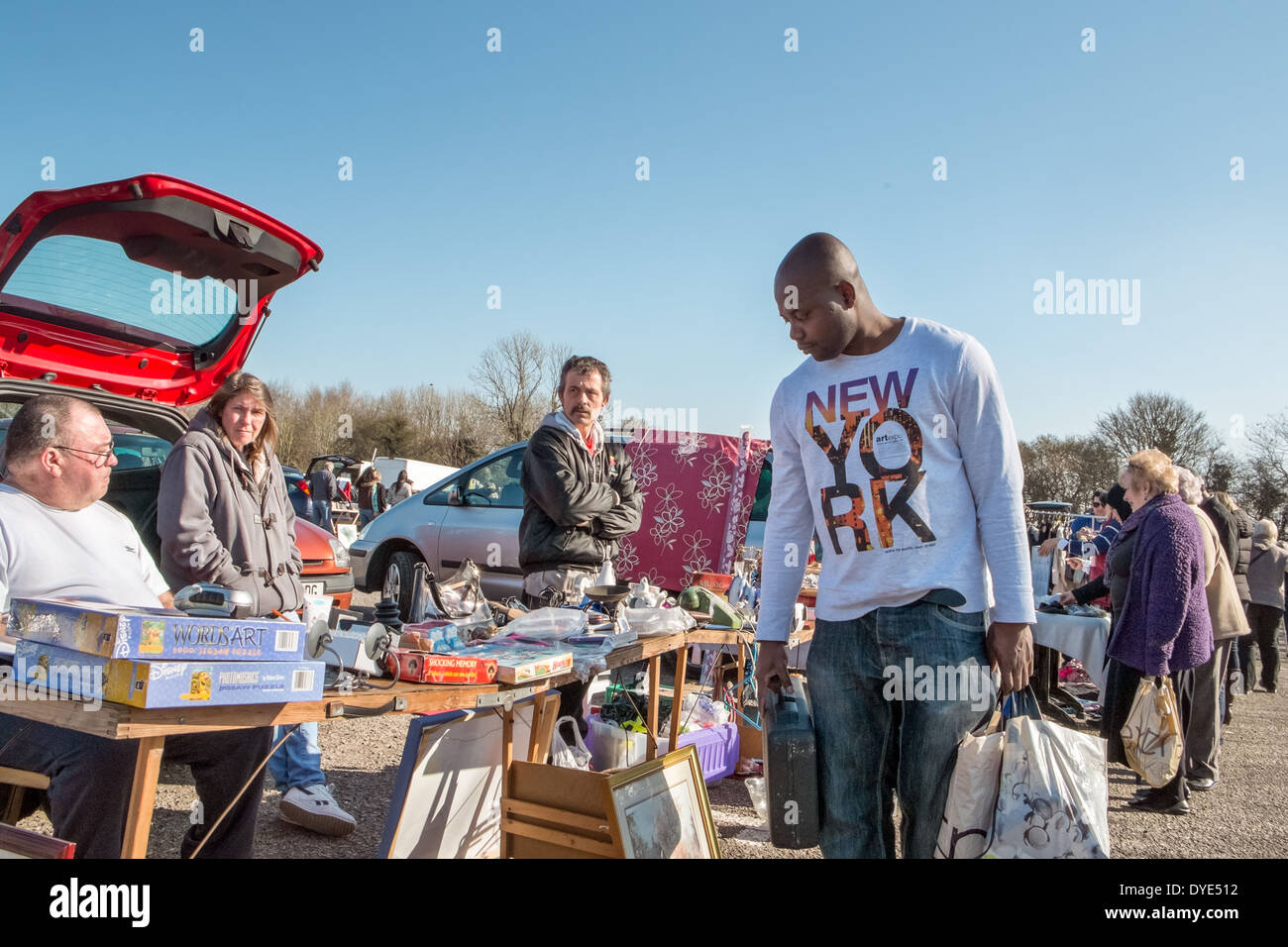 A man browsing a bric a brac stall at an open air car boot sale on a sunny day with vendors sitting in the boot of their car, UK - Stock Image