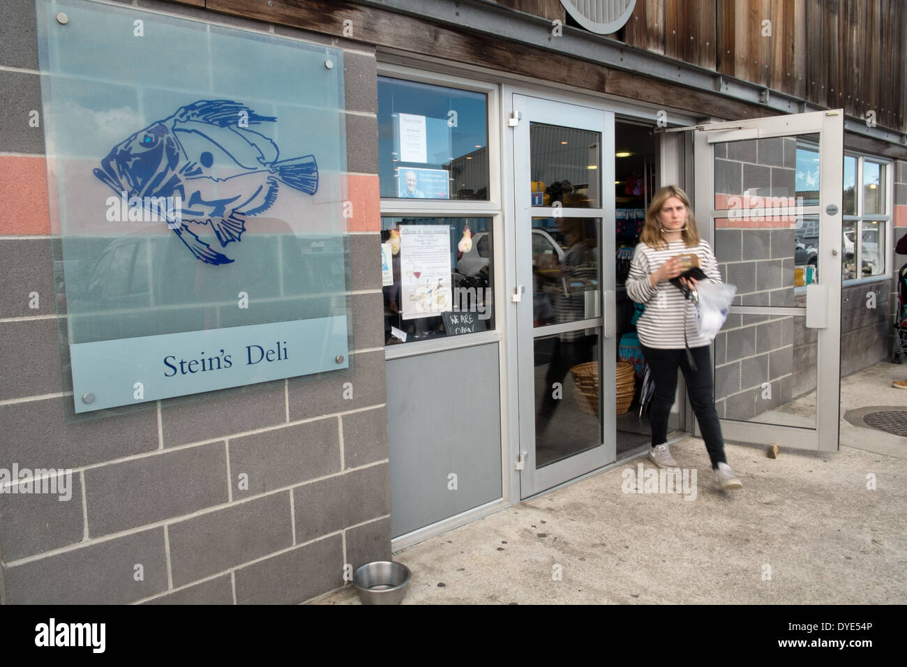 A customer leaving Cornish chef, Rick Stein's deli in Padstow, Cornwall, UK. The shop sign displays his group logo - Stock Image