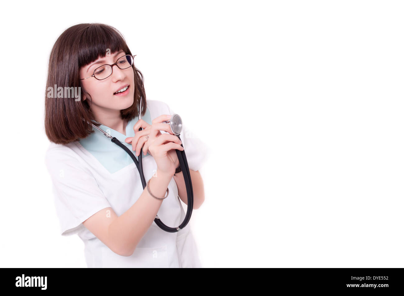 Young female doctor holding stethoscope and smiling - Stock Image