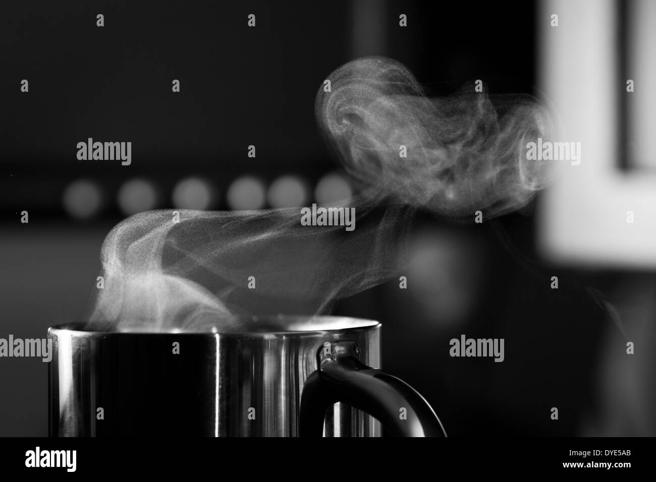Steam rises from a mug of hot coffee - Stock Image