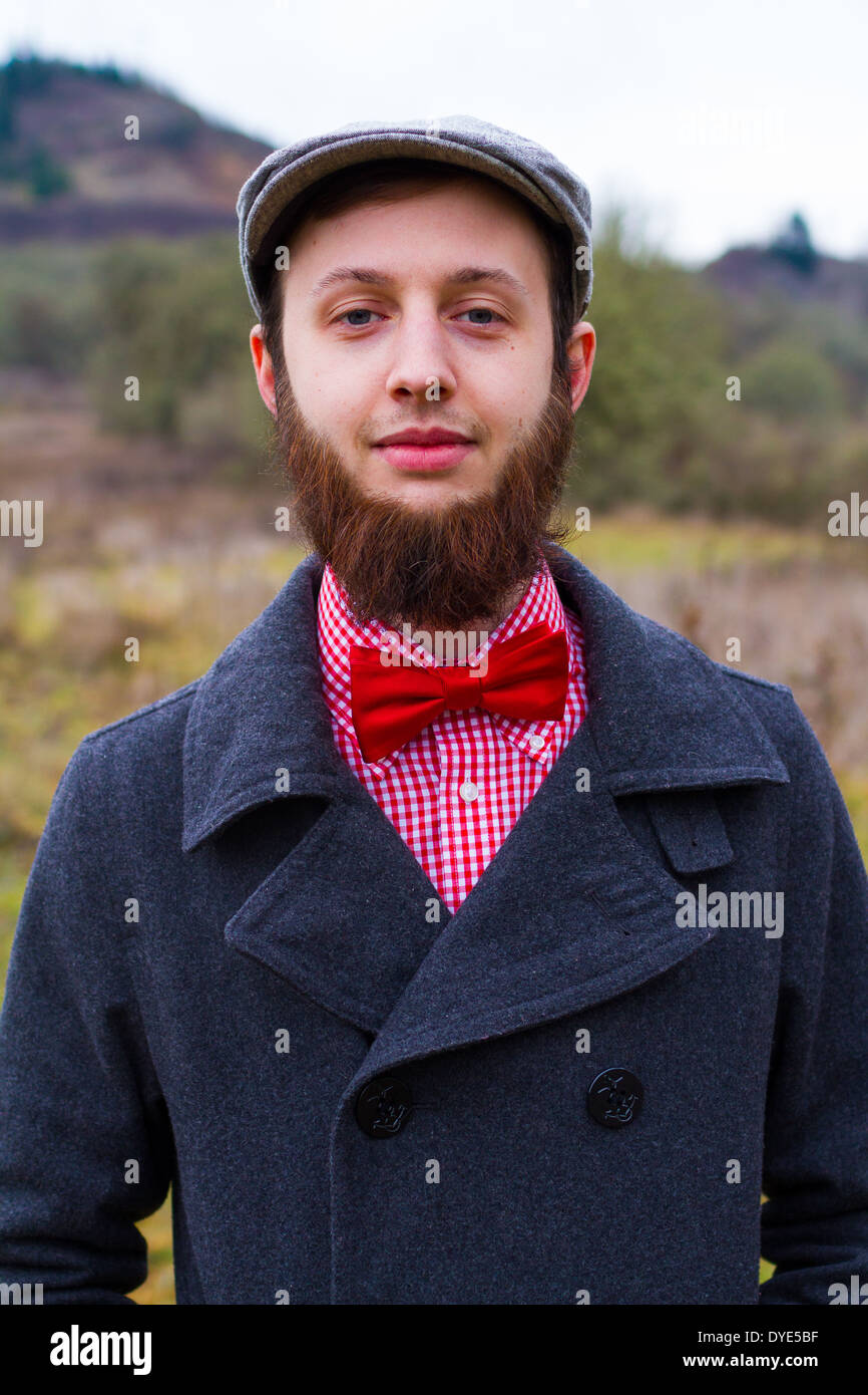 Trendy hipster guy outdoors in the winter in a fashion portrait of the handsome man. - Stock Image
