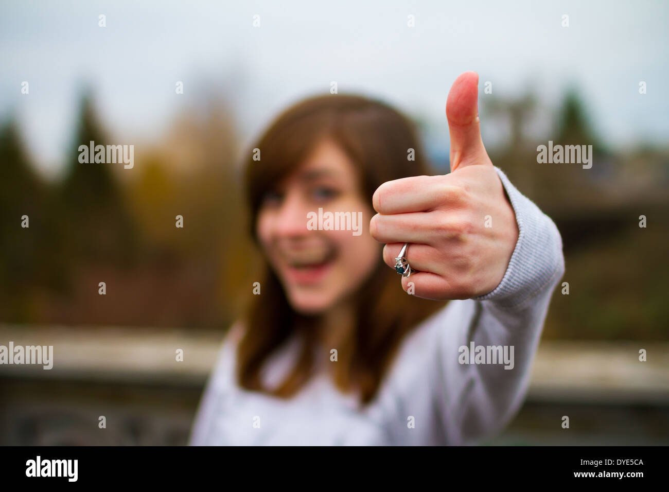 Beautiful girl doing a thumbs up sign with her hand and fingers for this unique approval image. - Stock Image