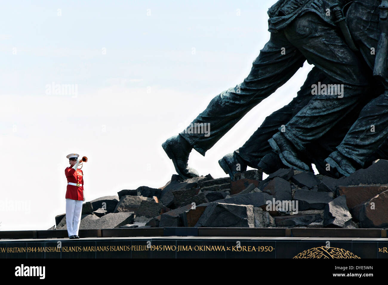 US Marine Corps Staff Sgt. Codie Williams plays the bugle near the giant feet of the Marine Corps War Memorial during Stock Photo