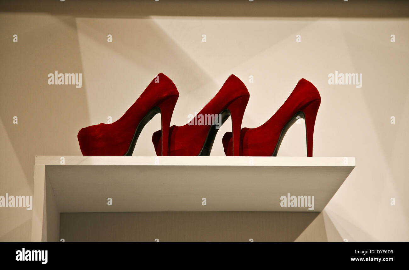 Fashionable woman's red high heel stiletto shoes on a shelf, high heels close up - Stock Image