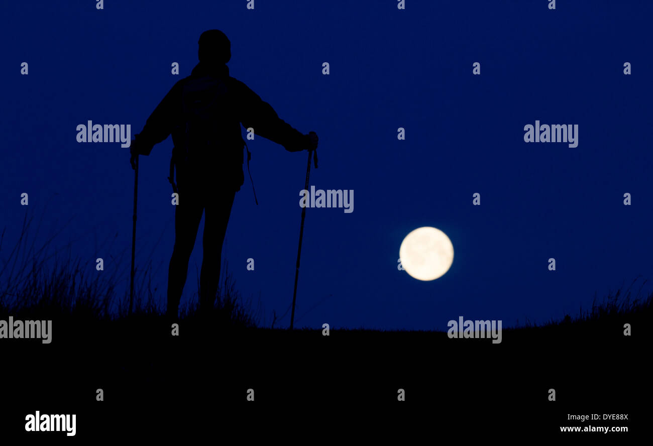 Hiker on mountain silhouetted against full moon - Stock Image