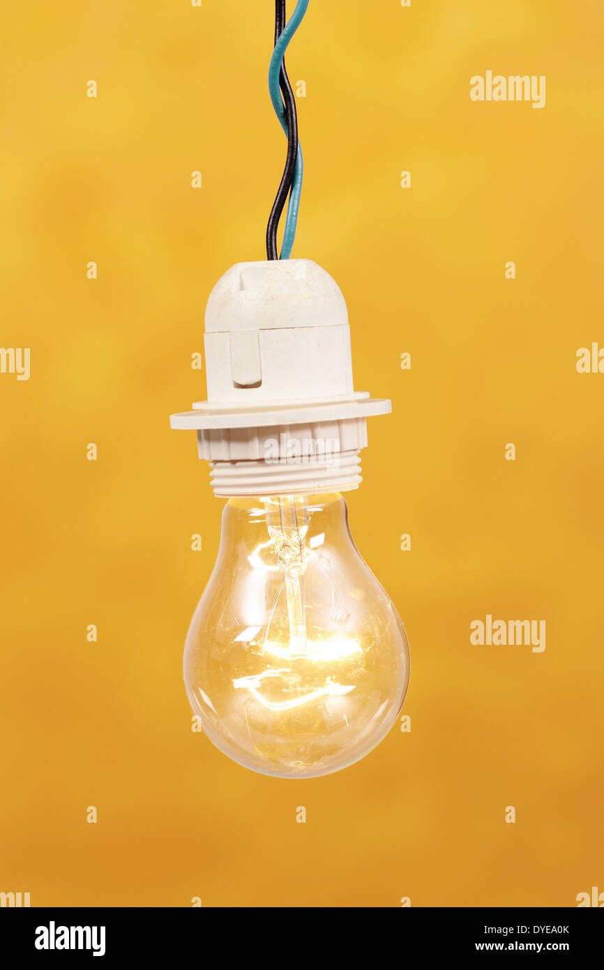 a light bulb lit on a yellow background - Stock Image