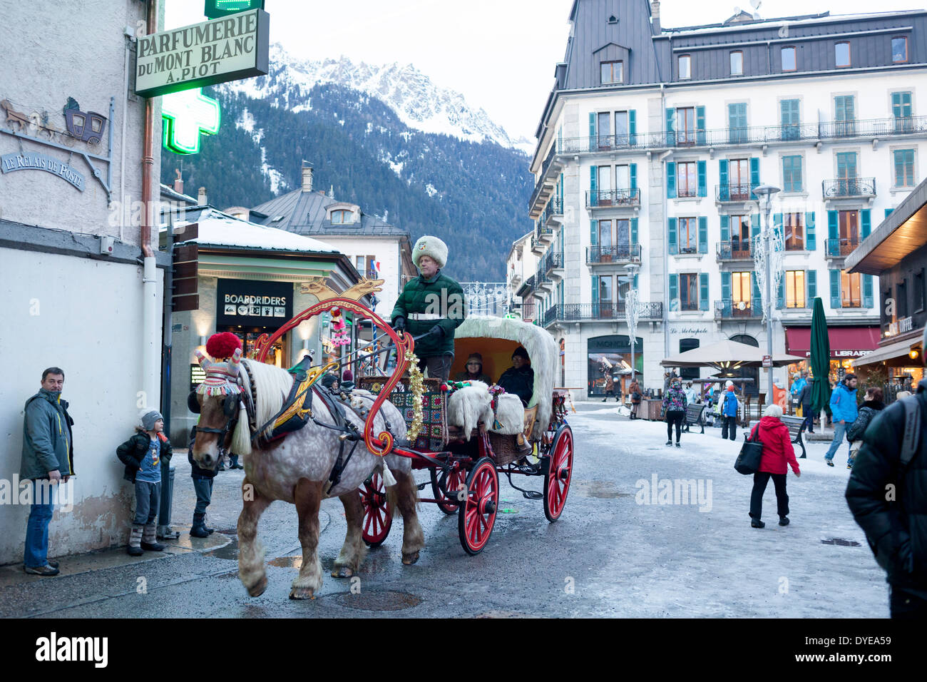 Pedestrians walk past a horse drawn buggy covered in fur on the Rue du Docteur Paccard in the village of Chamonix Mont-Blanc. - Stock Image