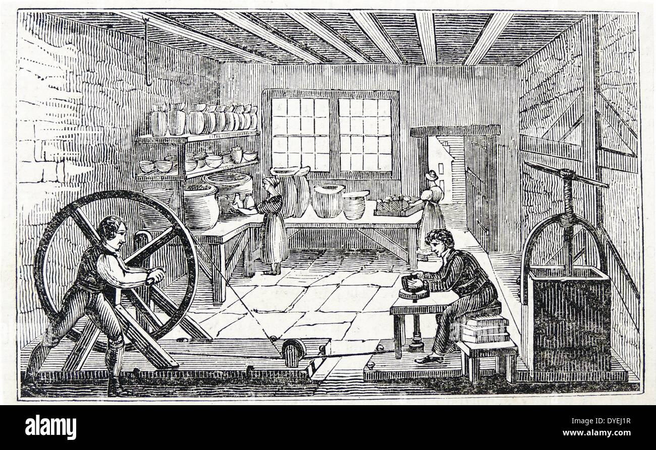 A potter's workshop: Boy turns wheel woks the belt which rotates the potter's wheel. Woodcut, London, 1936. - Stock Image