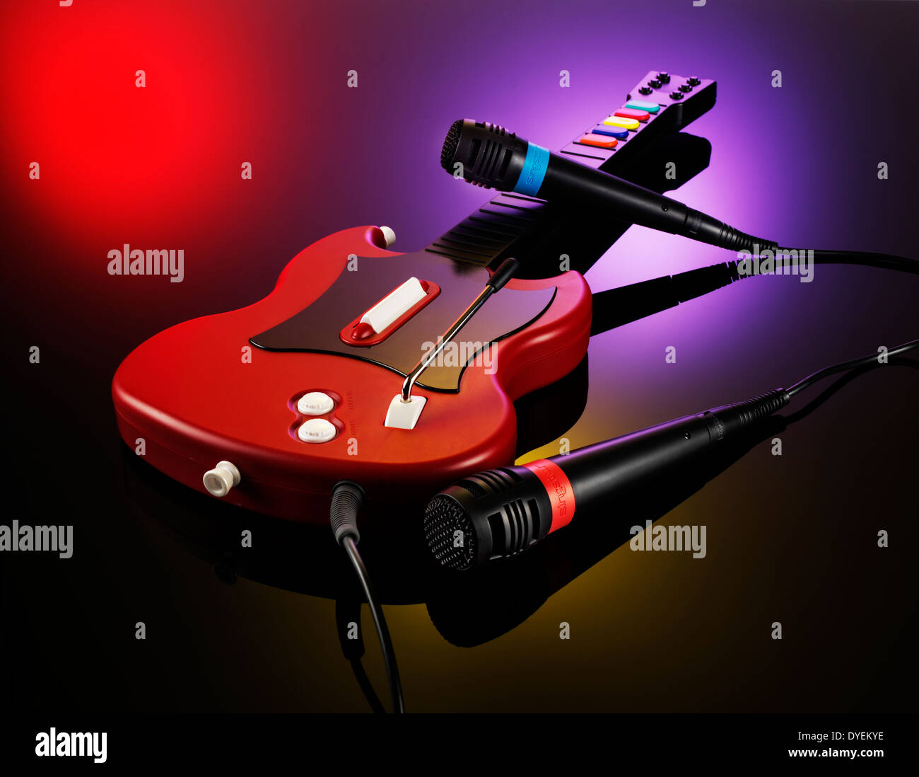 TWO MICROPHONES AND A GUITAR FROM THE VIDEO GAME GUITAR HERO ON A PINK BLACK RED BACKGROUND - Stock Image