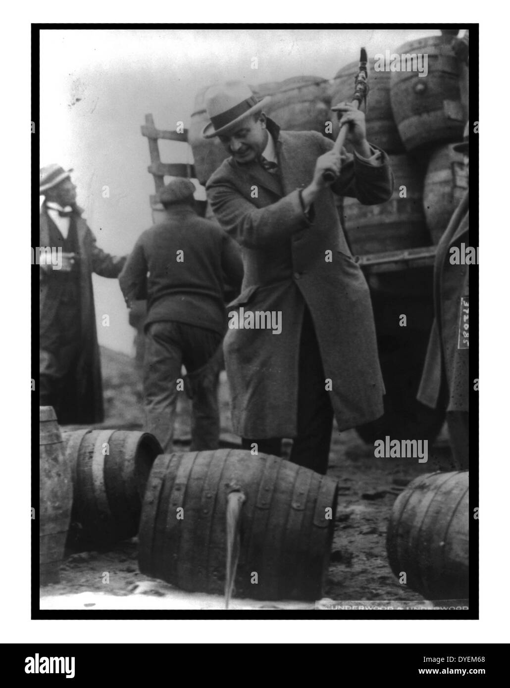 FBI Officer breaks a confiscated barrel of beer as part of the prohibition campaign against alcohol - Stock Image