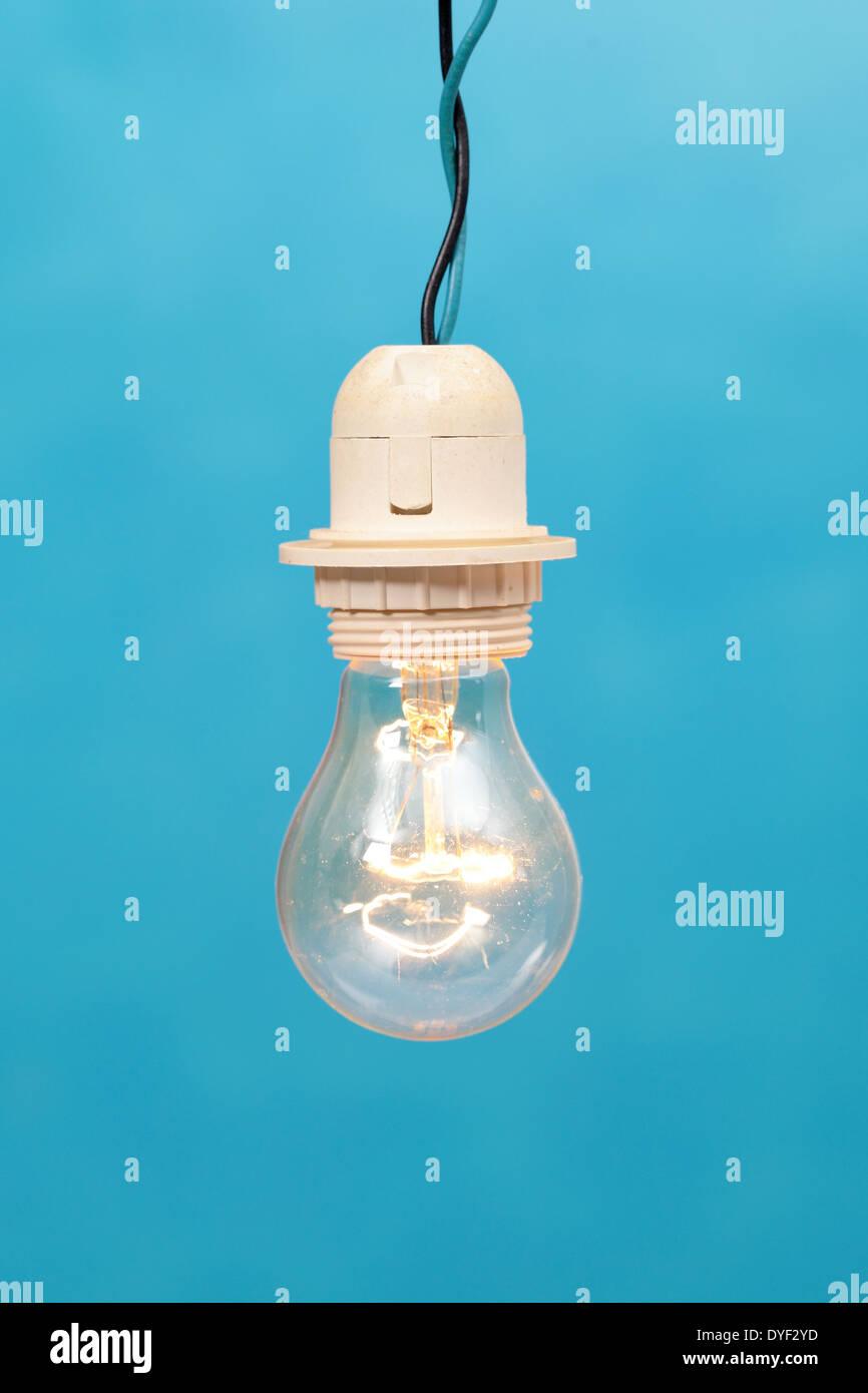 a light bulb lit on a blue background - Stock Image