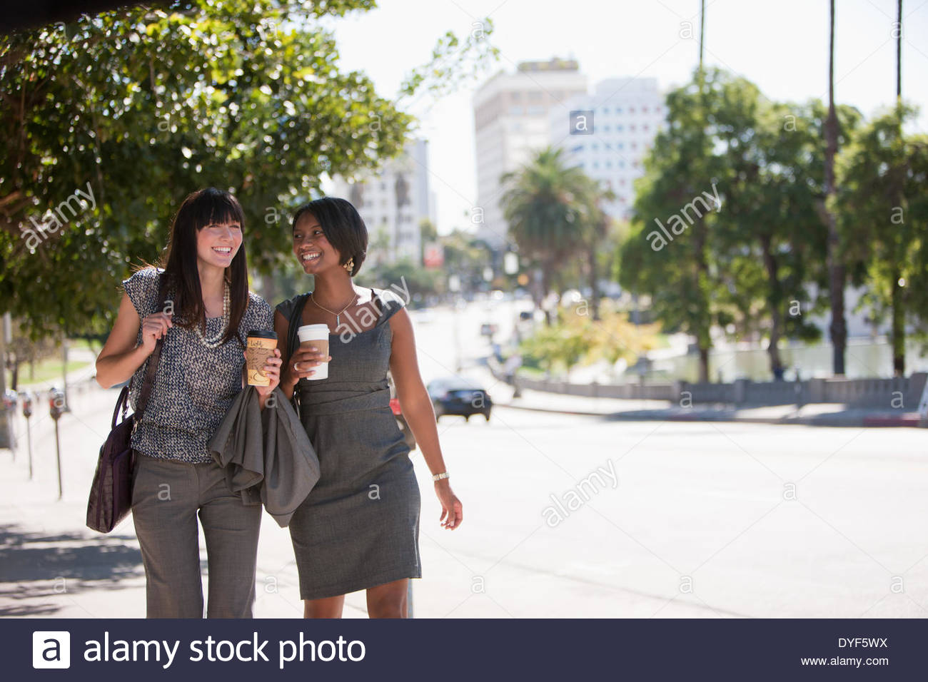 Businesswomen walking together outdoors - Stock Image