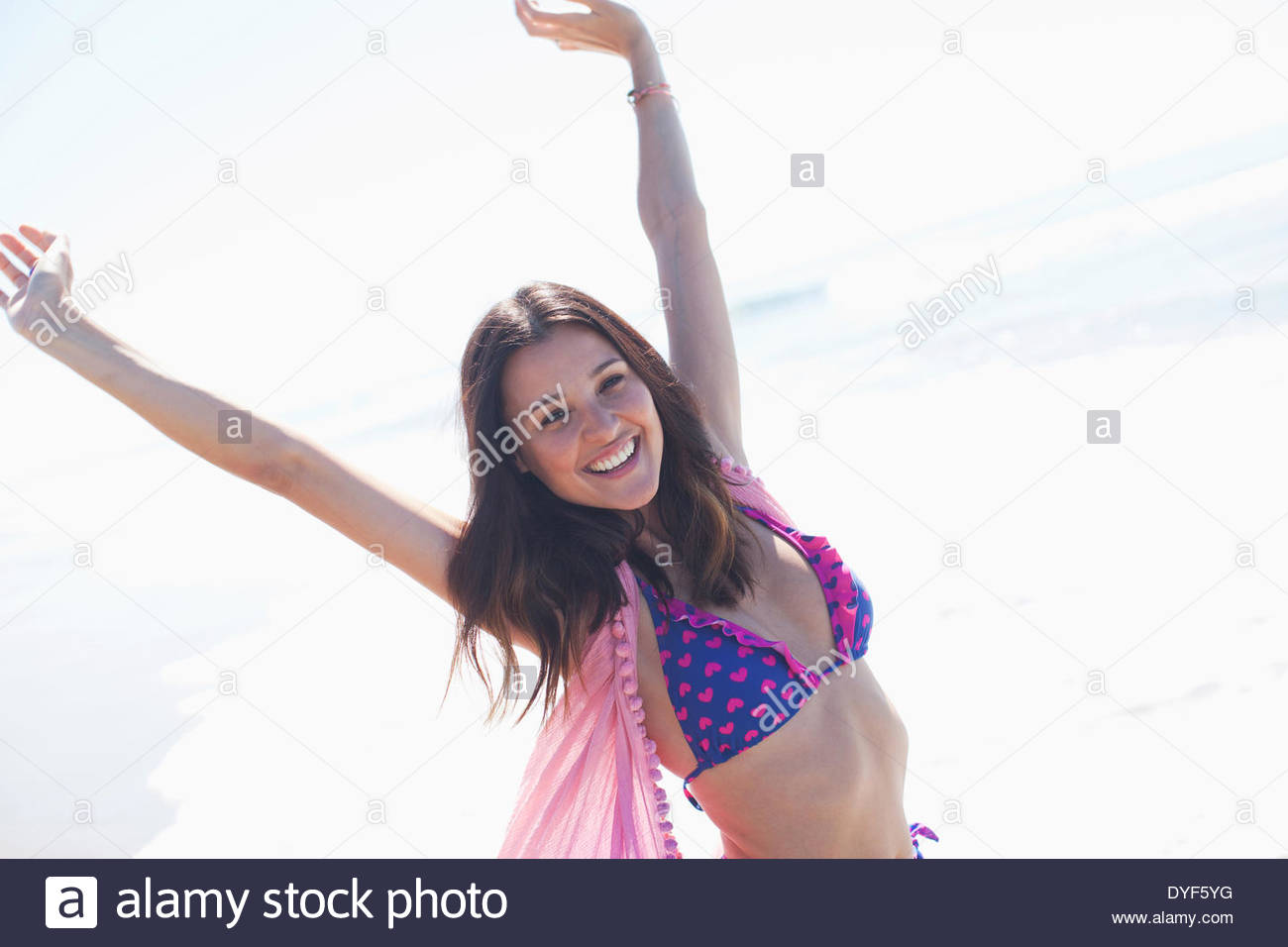 Smiling woman standing on beach - Stock Image