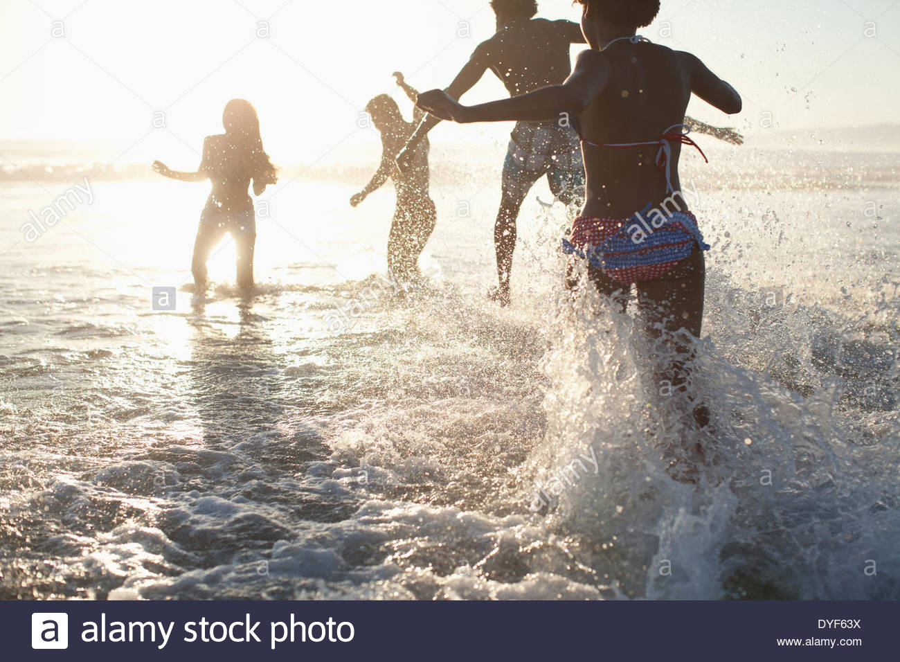 Friends playing in waves on beach - Stock Image