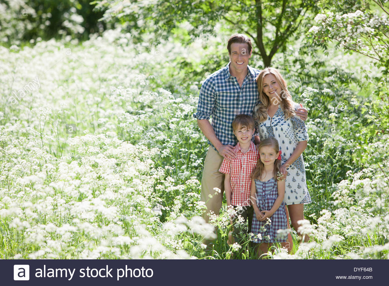 Family standing together in field of flowers - Stock Image