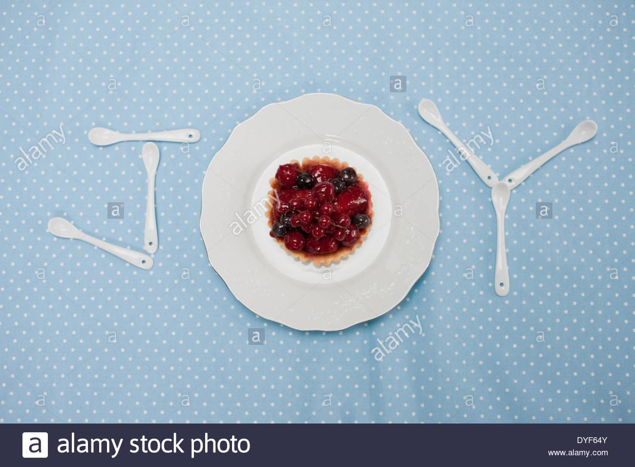 Teaspoons plate cupcake spelling joy on tablecloth - Stock Image