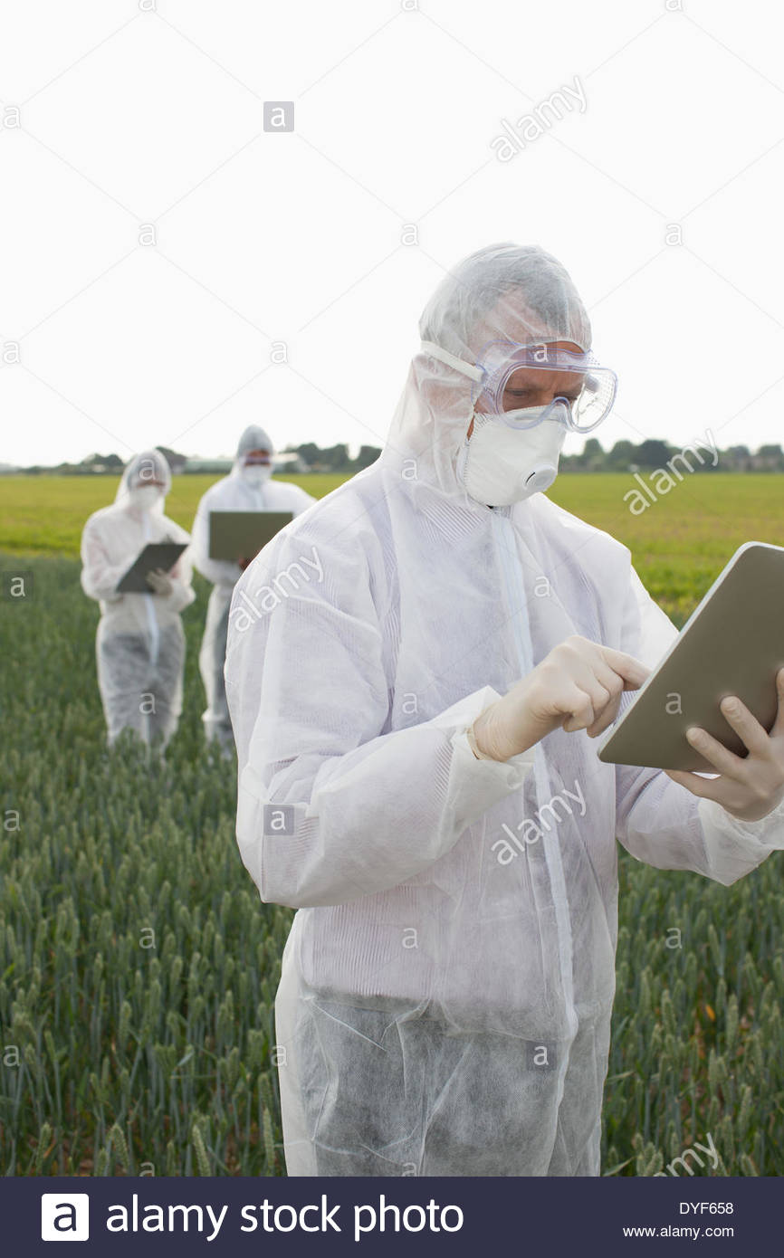 Scientist in protective gear using tablet computer - Stock Image