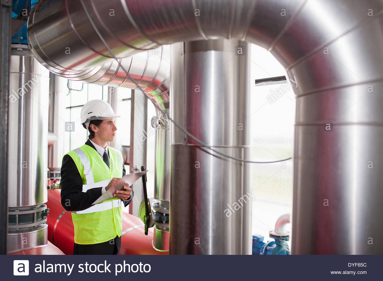 Scientist with clipboard in warehouse - Stock Image
