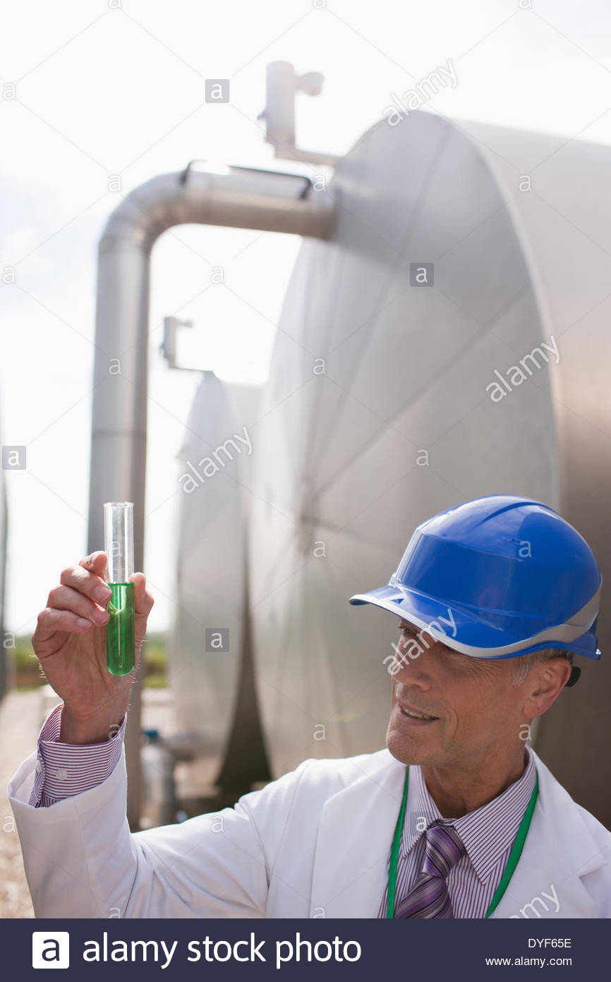 Scientist examining liquid in test tube - Stock Image