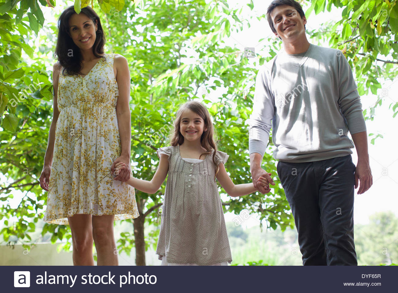 Family holding hands together outdoors - Stock Image