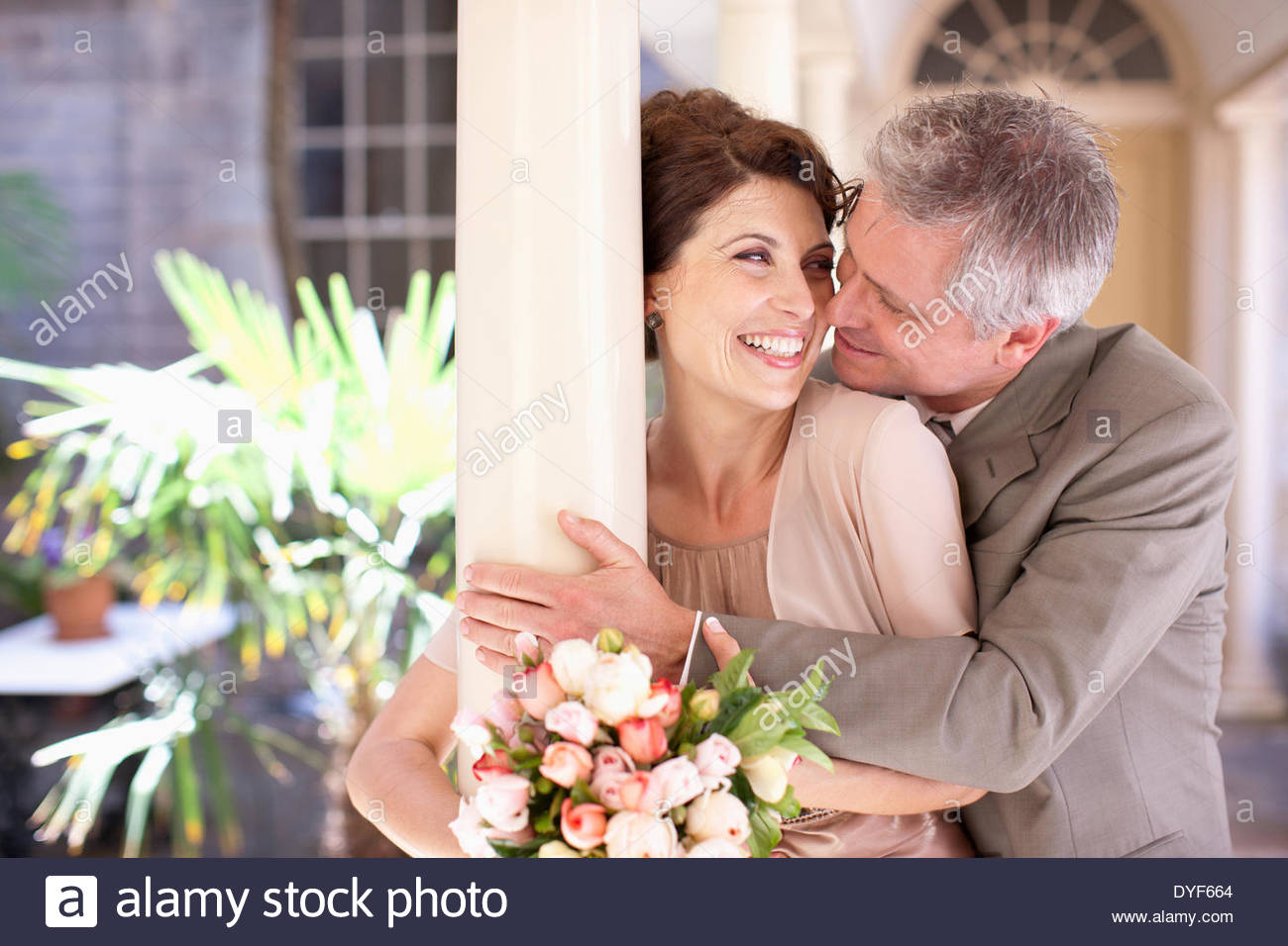 Mature bride and groom hugging - Stock Image