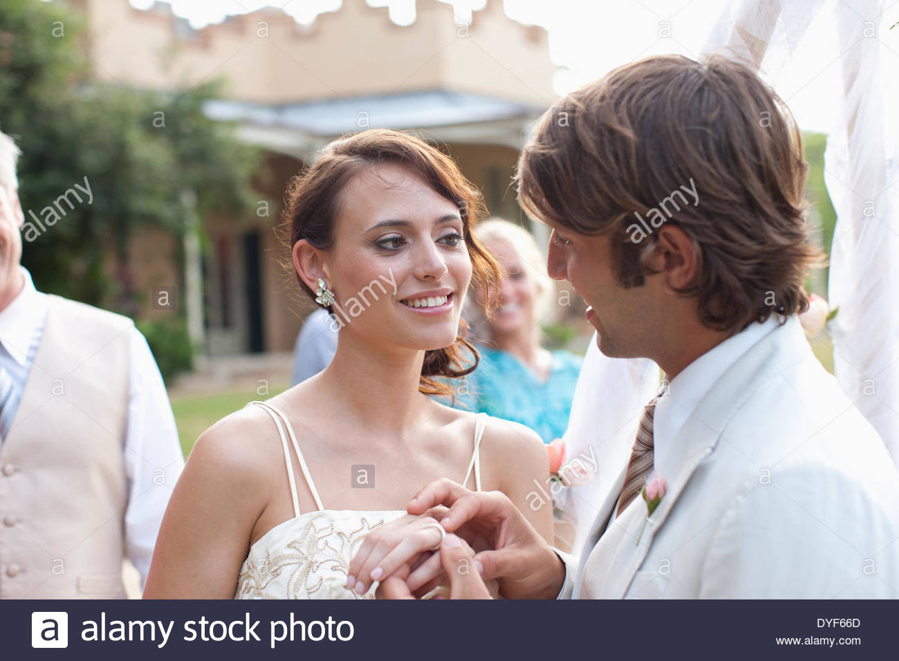 Groom putting ring on brideÂ's finger - Stock Image