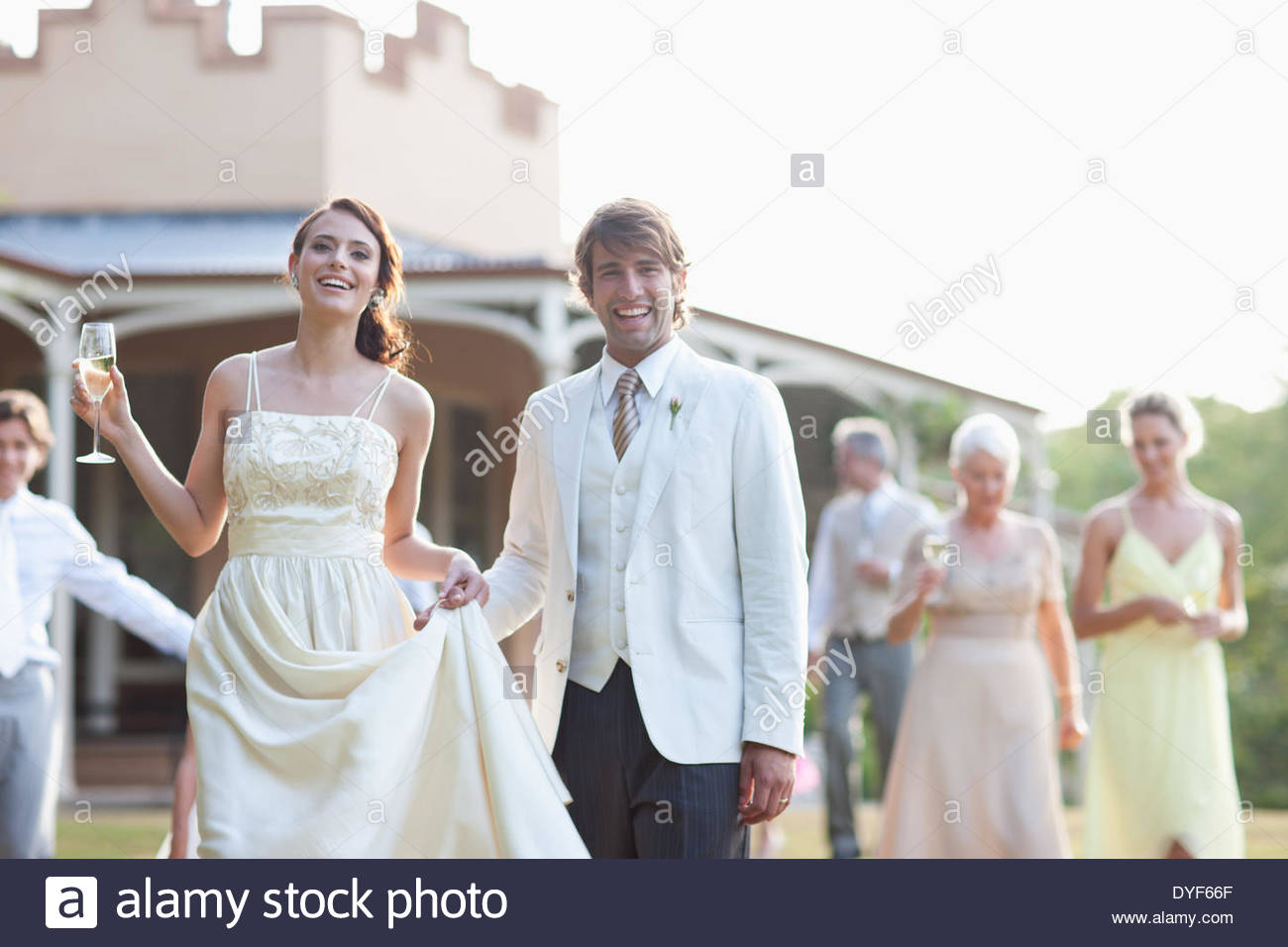 Bride, groom and guests walking across lawn - Stock Image