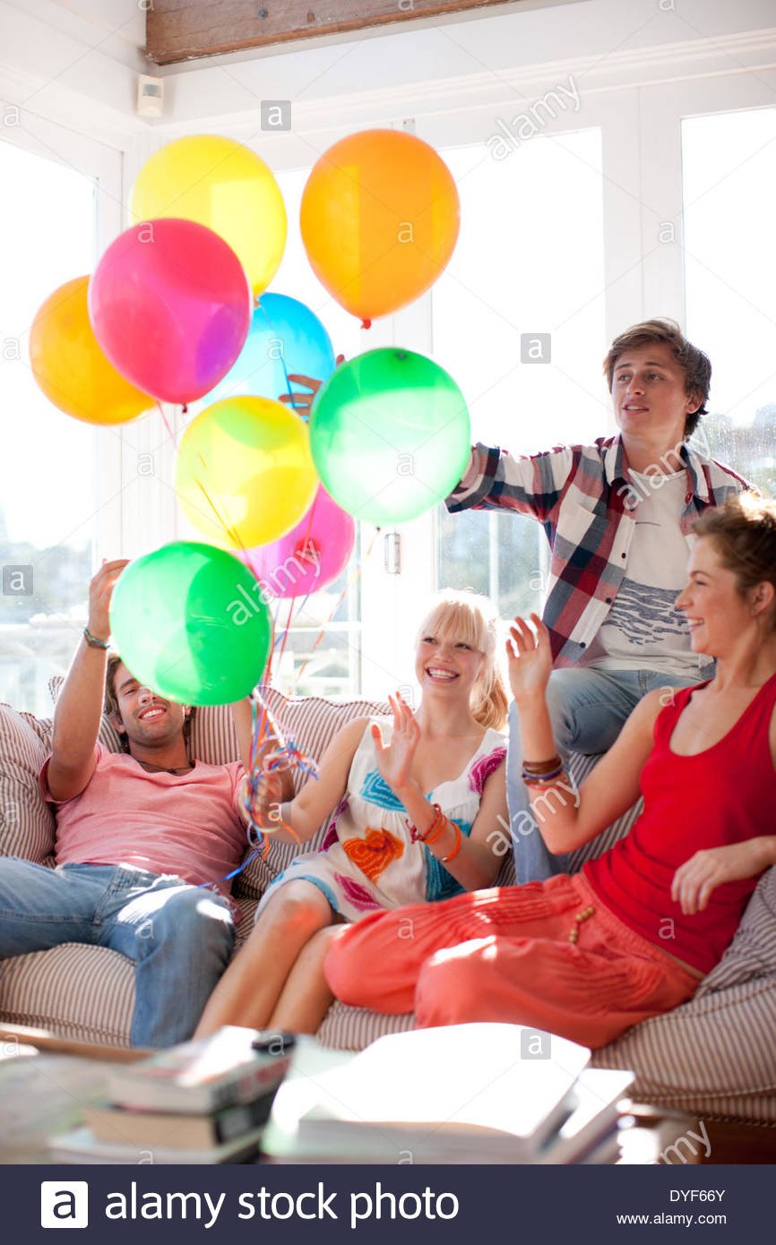 Friends balloons sitting on sofa in living room - Stock Image