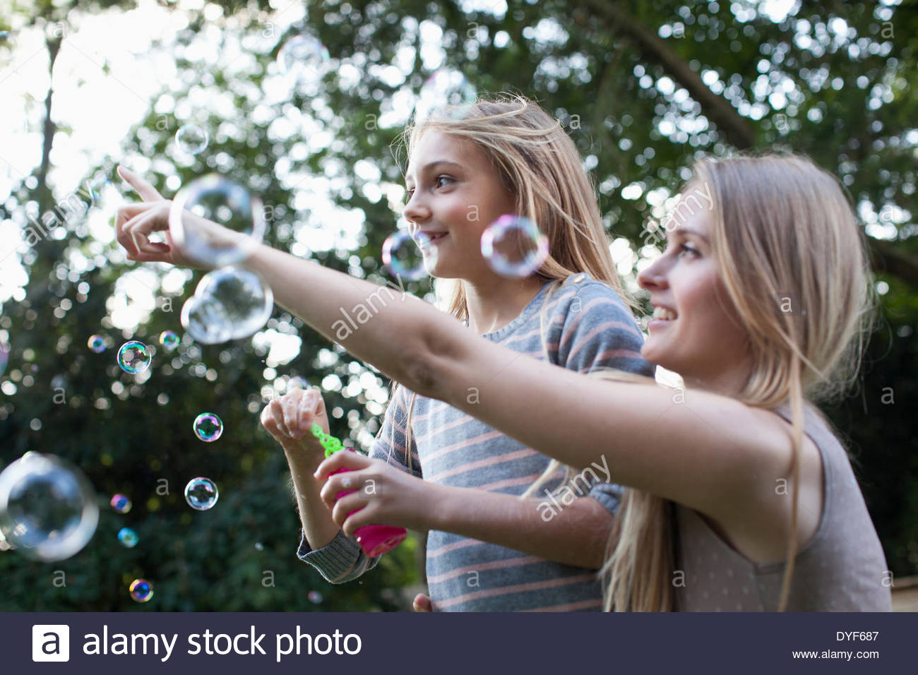 Mother and daughter blowing bubbles under tree - Stock Image