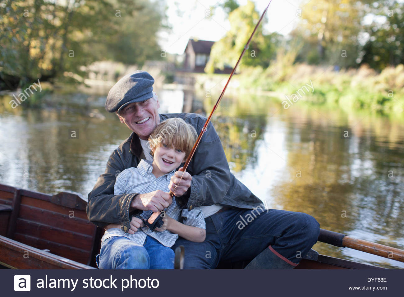 Grandfather and grandson fishing in boat - Stock Image