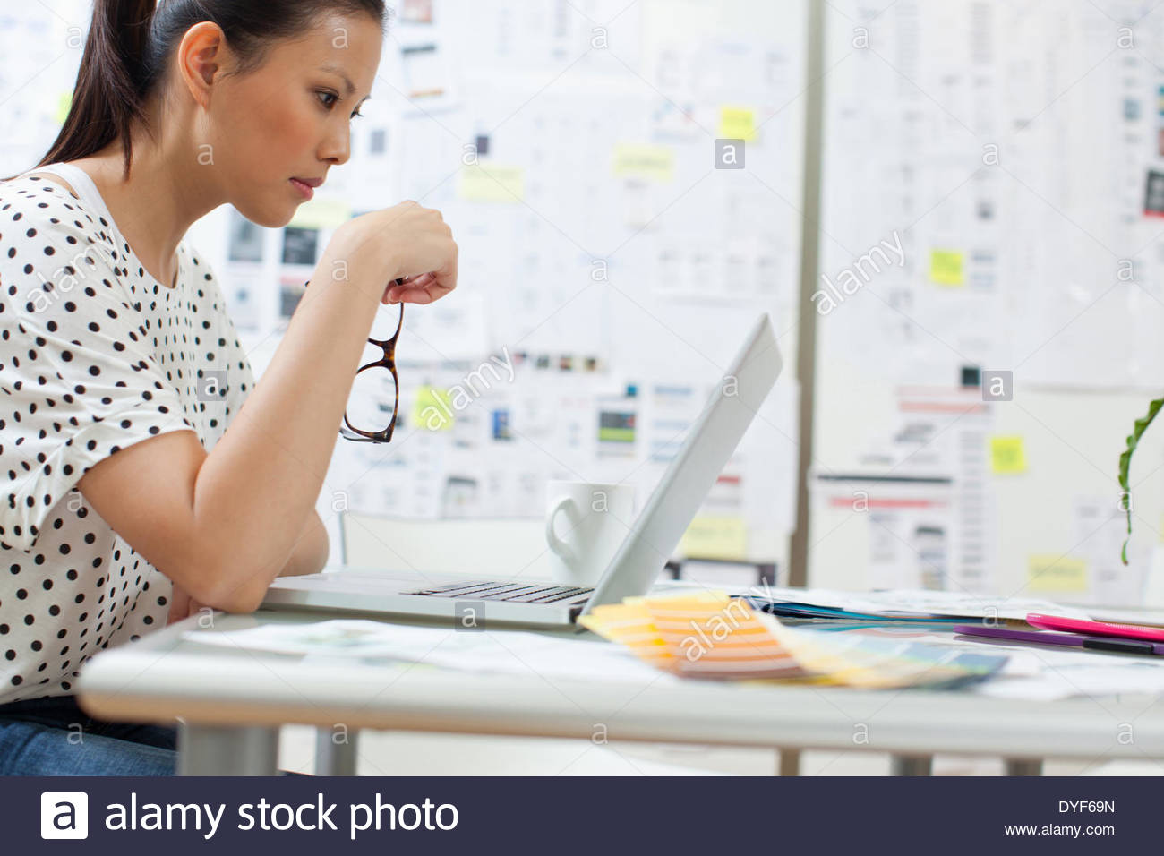 Serious businesswoman looking down laptop in office - Stock Image