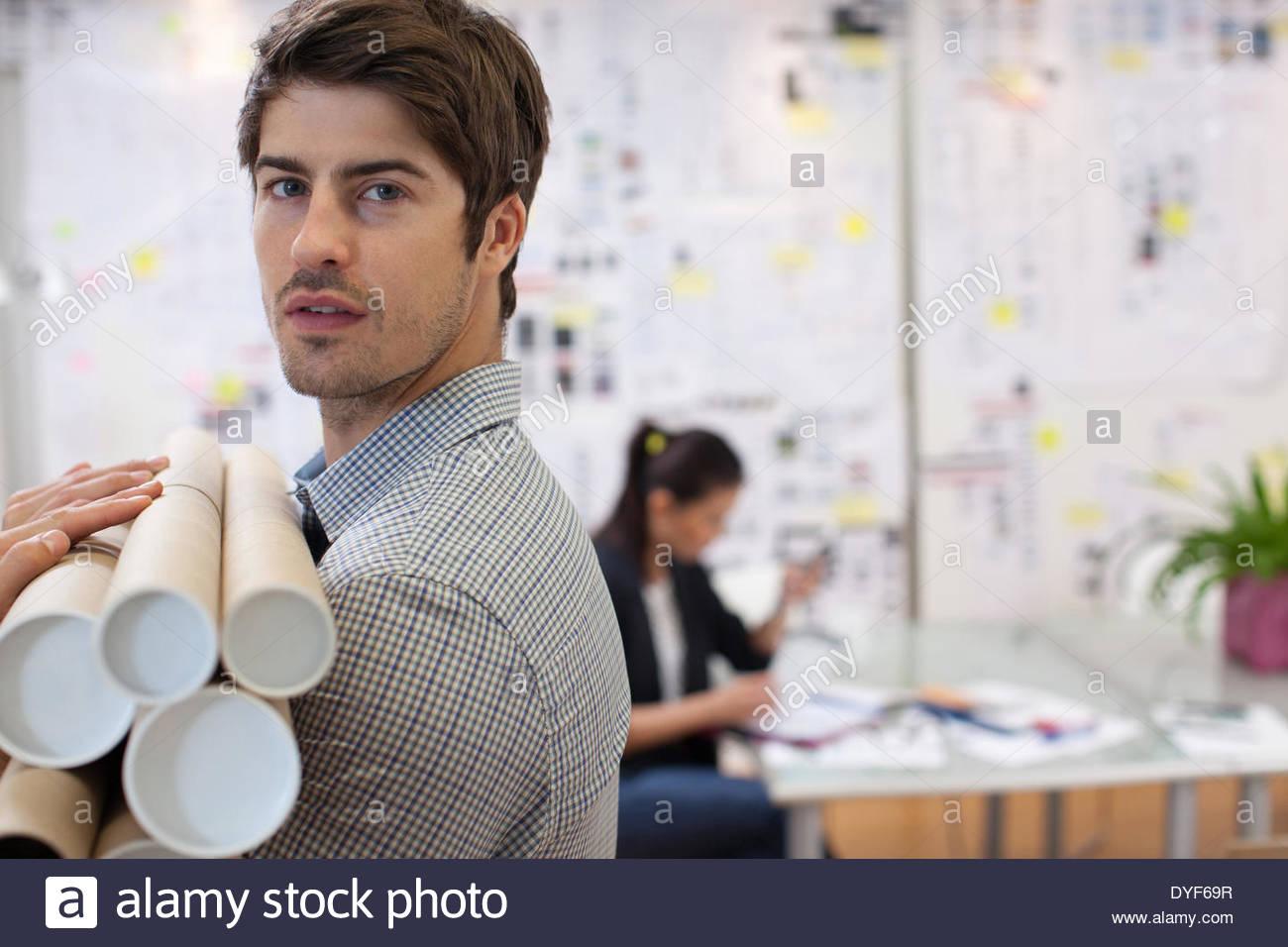 Portrait architect holding blueprint tubes in office - Stock Image